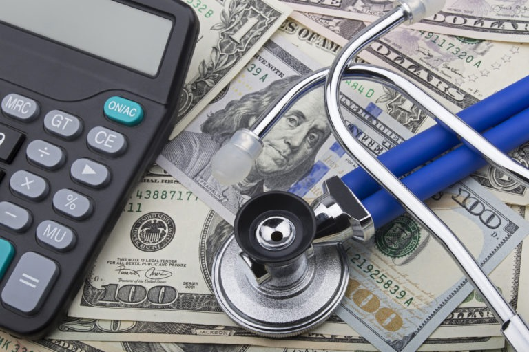 cash, calculator and stethoscope